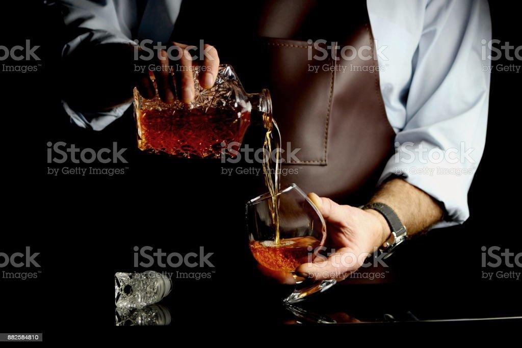 мужчина наливает коньяк stock photo