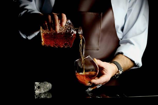 мужчина наливает коньяк мужчина наливает коньяк в бокал за барной стойкой brandy stock pictures, royalty-free photos & images