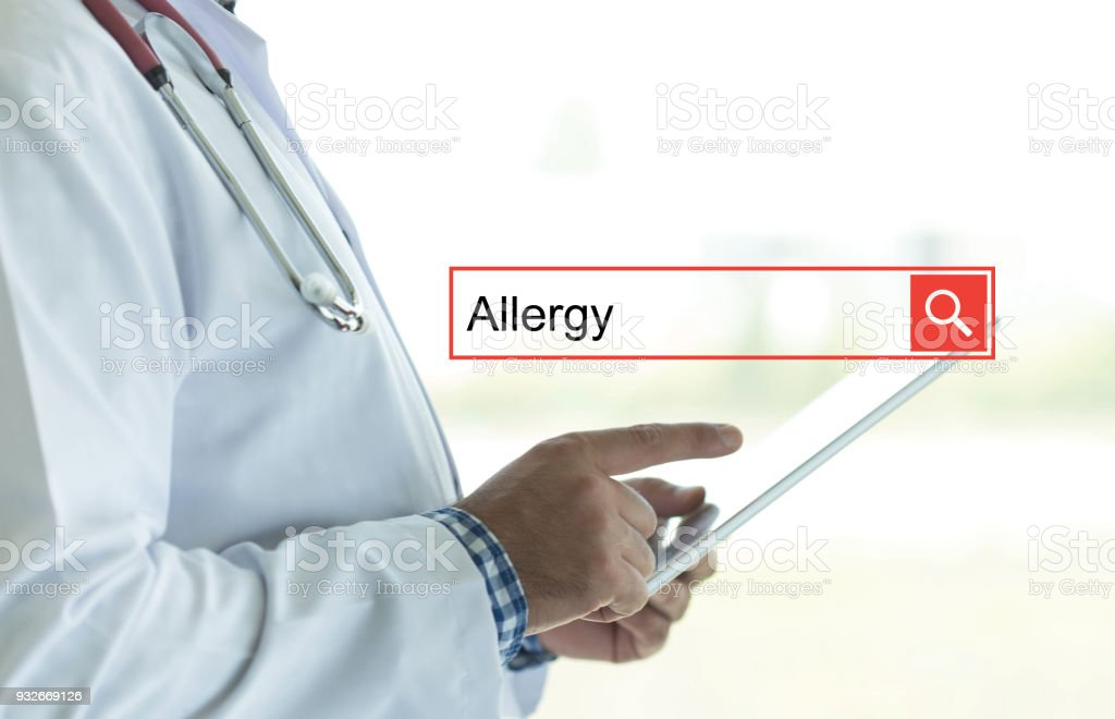 DOCTOR USING TABLET PC AND SEARCHING ALLERGY ON WEB stock photo