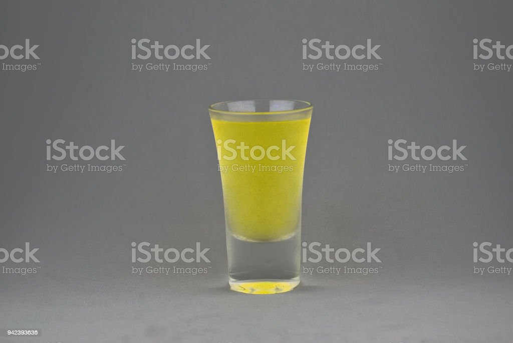 LEMONCELLO SHOT IN GREY BACKGROUND stock photo