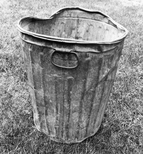 BENT METAL GARBAGE CAN ON A LAWN stock photo