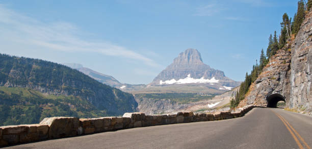 clements mountain with snow at the top of logan pass on the going to the sun highway under cirrus clouds during the 2017 fall fires in glacier national park in montana united states - going to the sun road stock pictures, royalty-free photos & images