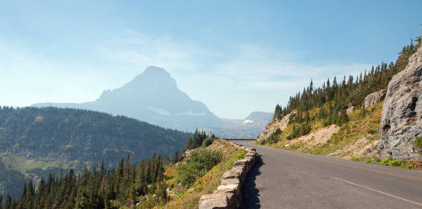 bearhat mountain at the top of logan pass on the going to the sun highway under cirrus clouds during the 2017 fall fires in glacier national park in montana united states - going to the sun road stock pictures, royalty-free photos & images