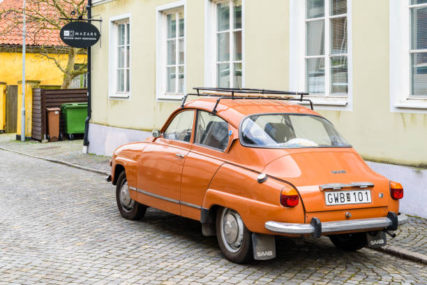 SAAB 96 Simrishamn, Sweden - April 27, 2018: Travel documentary of everyday life and environment. Vintage orange SAAB 96 V4 from 1974 with roof rack. Here on cobblestone street in the city. saab stock pictures, royalty-free photos & images