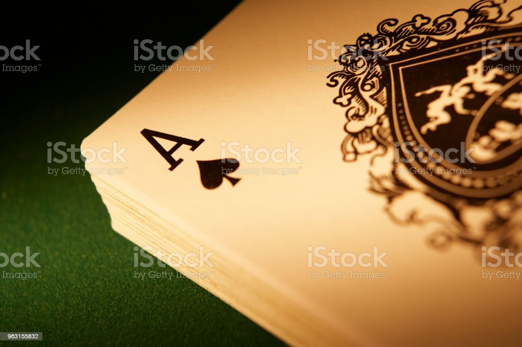 DECK OF PLAYING CARDS WITH ACE OF SPADES ON TOP IN CLOSE UP – zdjęcie