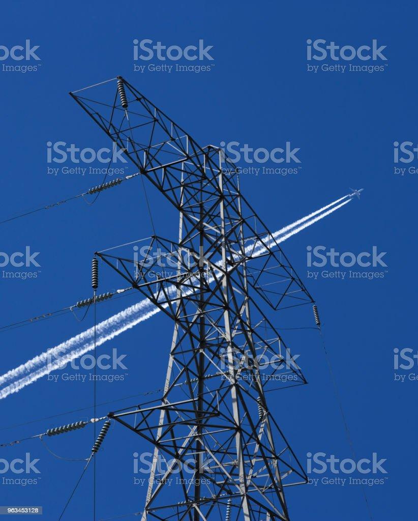 ELECTRICITY PYLON AND CABLES WITH AIRCRAFT EXHAUST TRAIL - Zbiór zdjęć royalty-free (Bez ludzi)