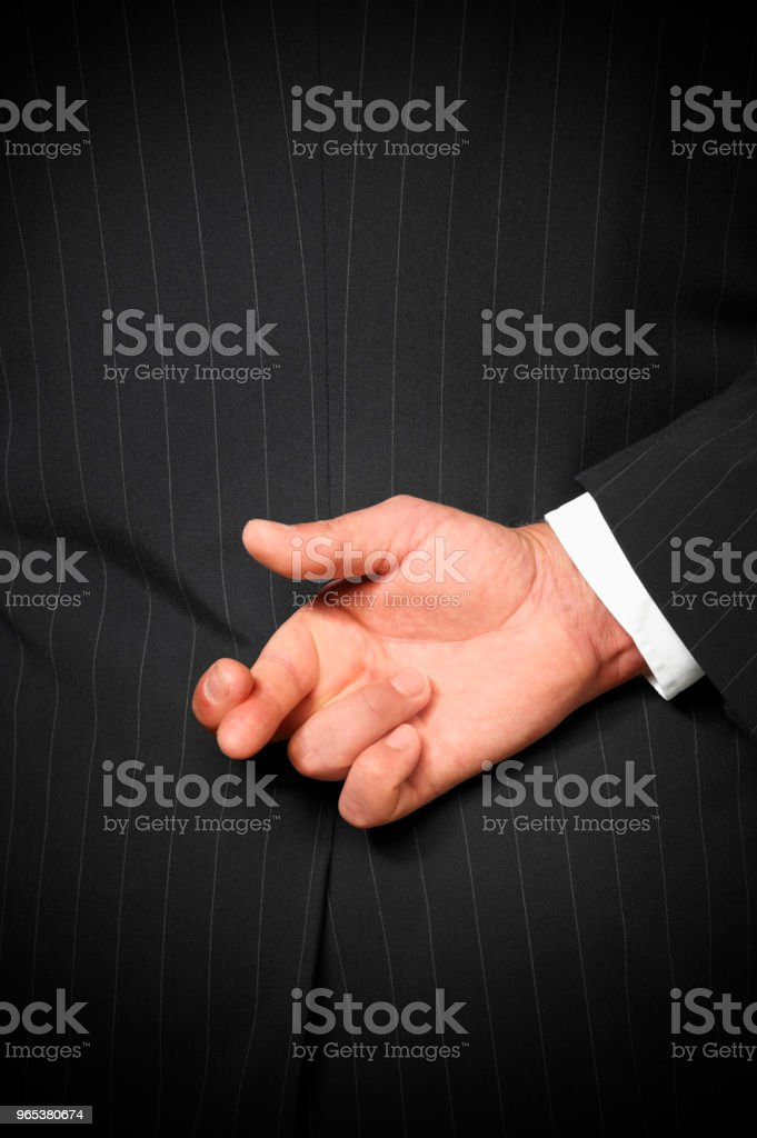 BUSINESS MAN WITH FINGERS CROSSED BEHIND BACK zbiór zdjęć royalty-free