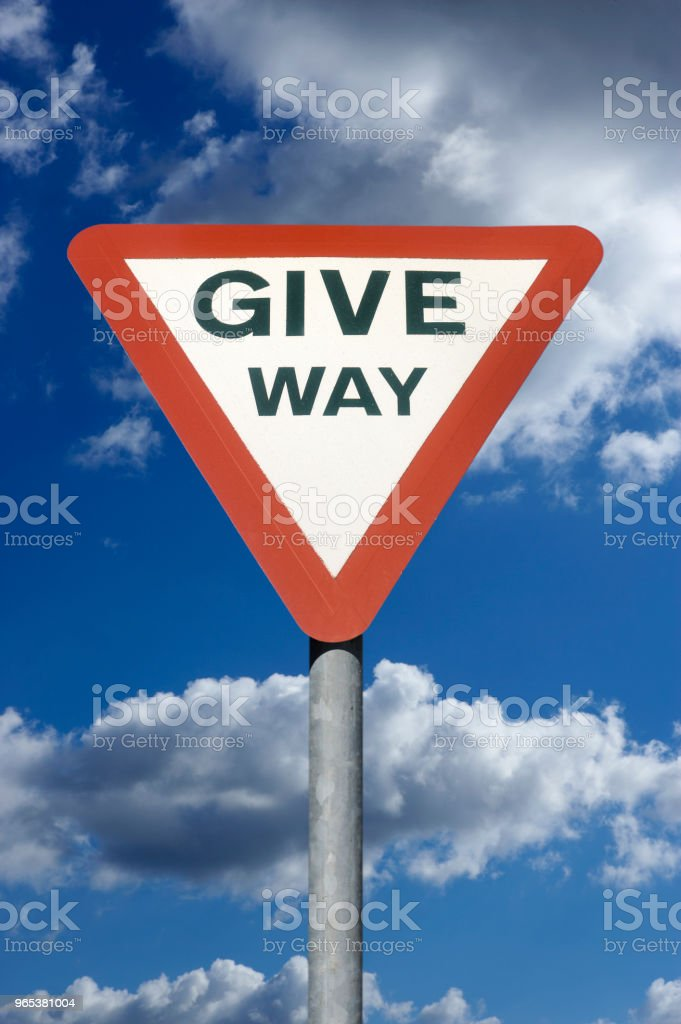 ROAD TRAFFIC GIVE WAY SIGN WITH BLUE SKY AND CLOUDS zbiór zdjęć royalty-free