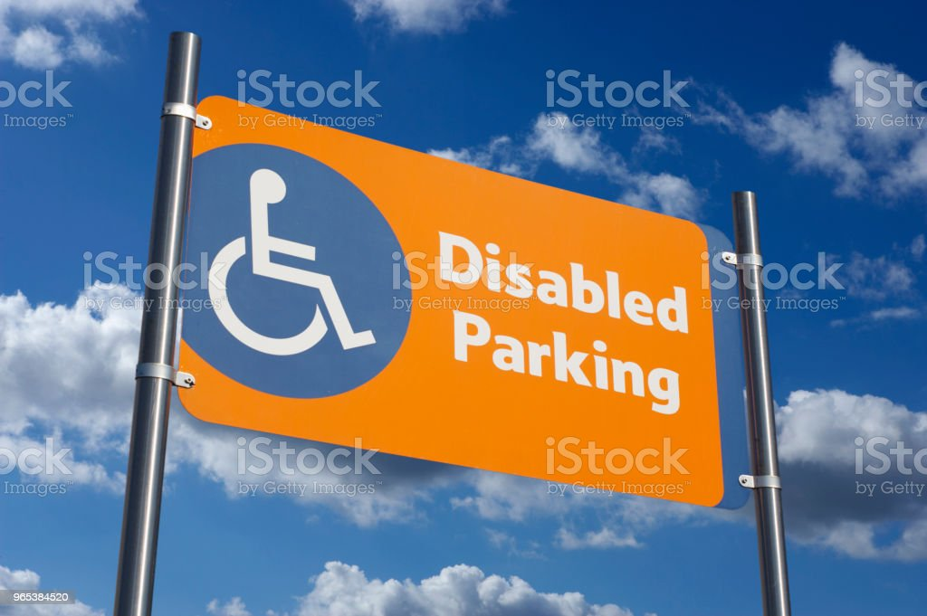 DISABLED PARKING SIGN WITH BLUE SKY AND CLOUDS zbiór zdjęć royalty-free