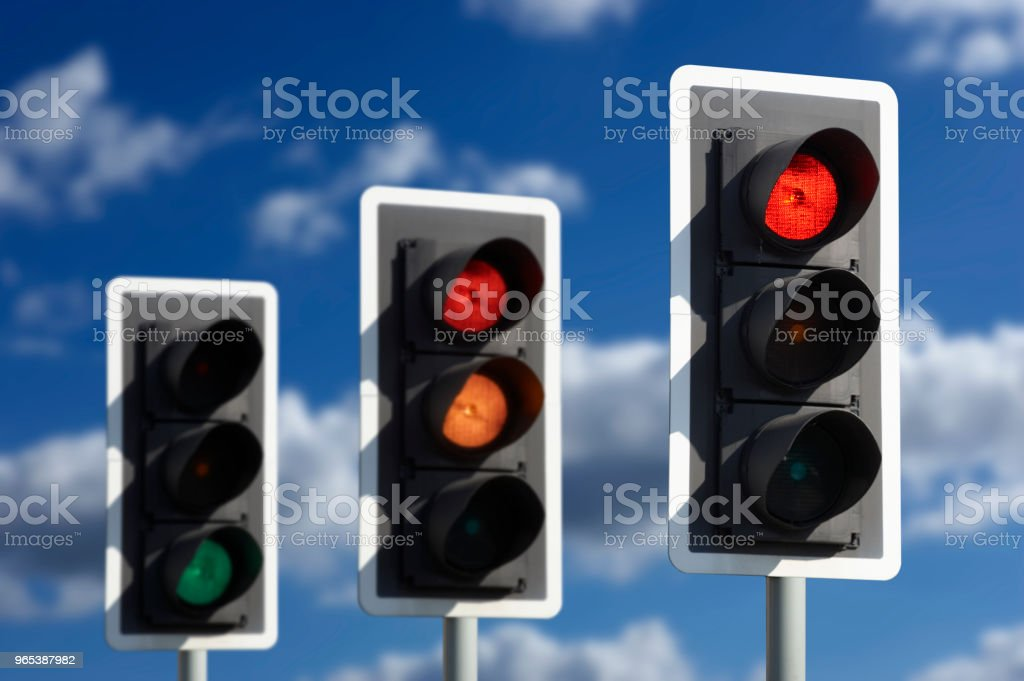 THREE TRAFFIC LIGHTS SHOWING RED AMBER AND GREEN royalty-free stock photo