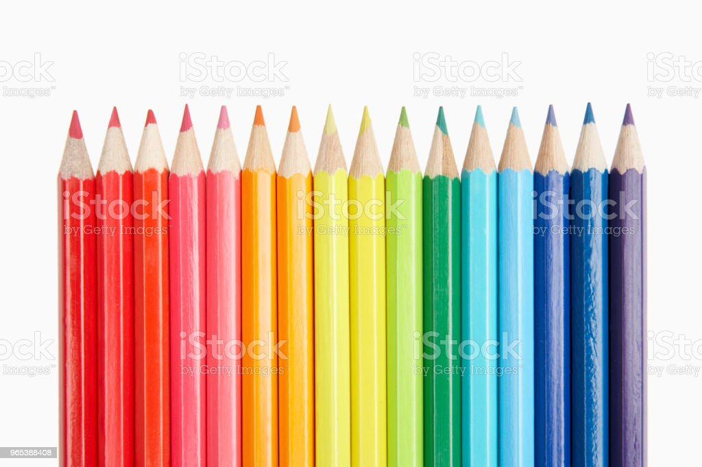 ROW OF COLOURED PENCILS ON WHITE BACKGROUND royalty-free stock photo