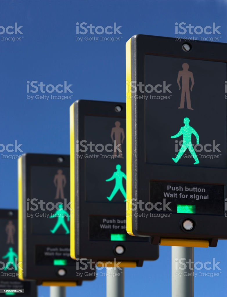 FOUR PEDESTRIAN CROSSING LIGHTS SHOWING GREEN royalty-free stock photo