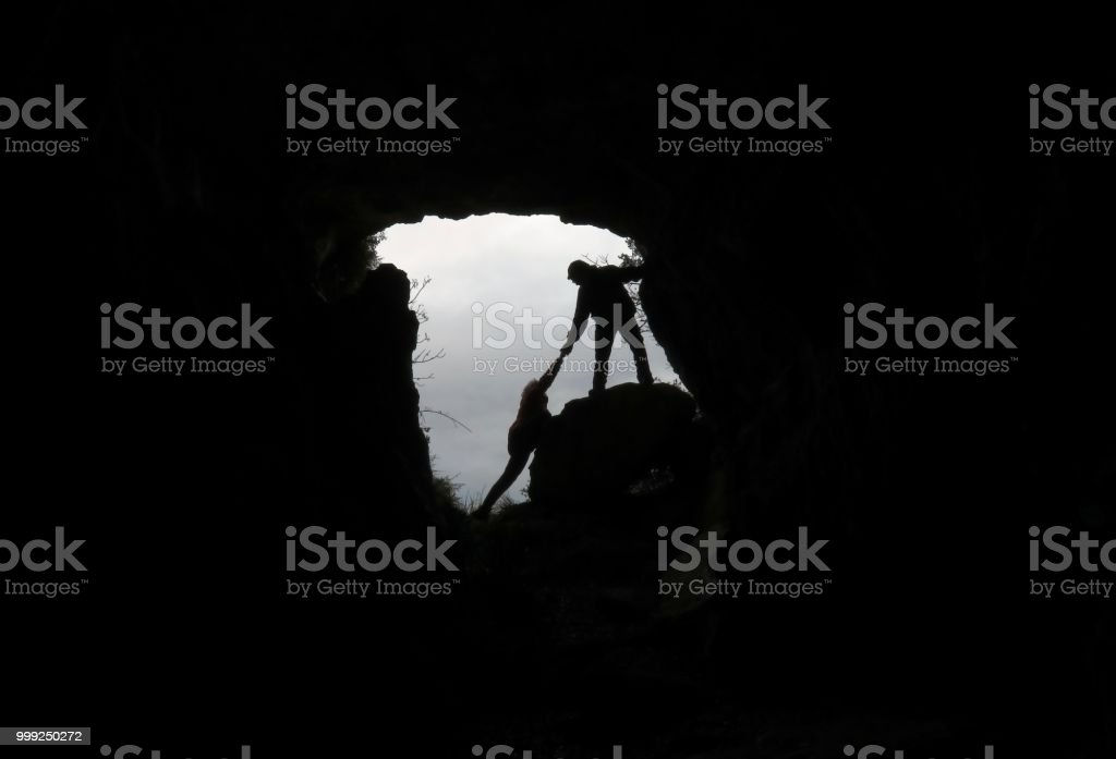 MAN RESCUING A PERSON IN A CAVE stock photo