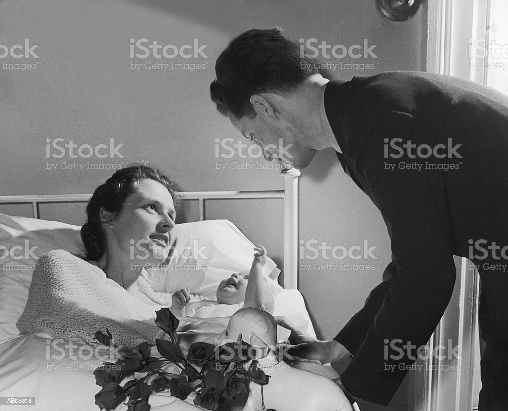 FATHER VISITING HIS WIFE & THEIR NEWBORN BABY IN HOSPITAL BED royalty-free stock photo