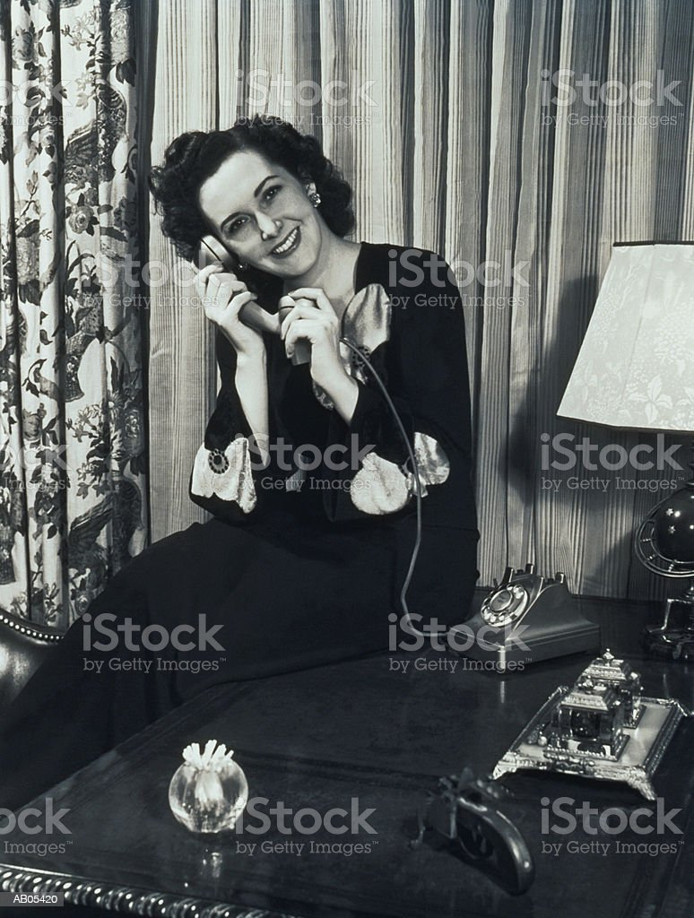 WOMAN SITTING IN LOUNGE, TALKING ON TELEPHONE royalty-free stock photo