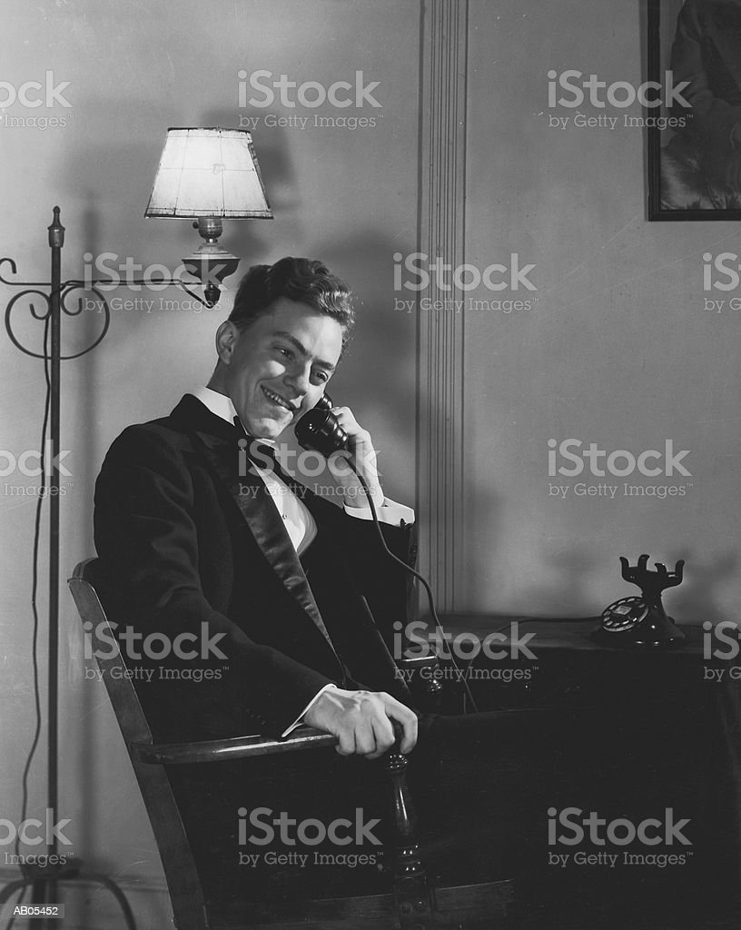 MAN IN DINNER SUIT SITTING INDOORS, TALKING ON TELEPHONE royalty-free stock photo