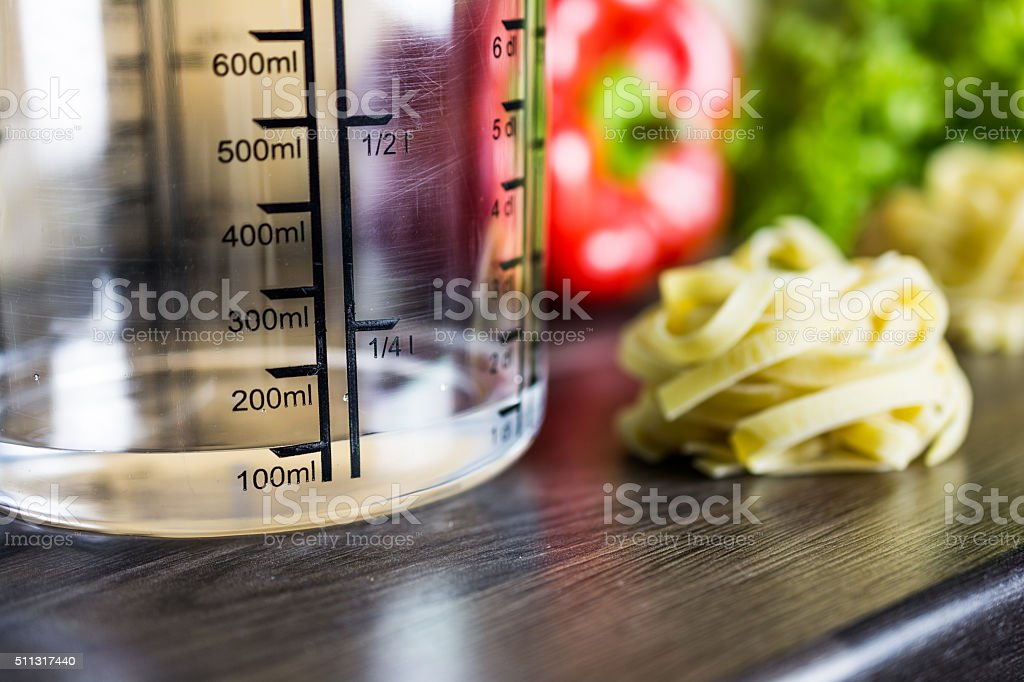 100ml Water In Measuring Cup On Kitchen Counter With Food stock photo