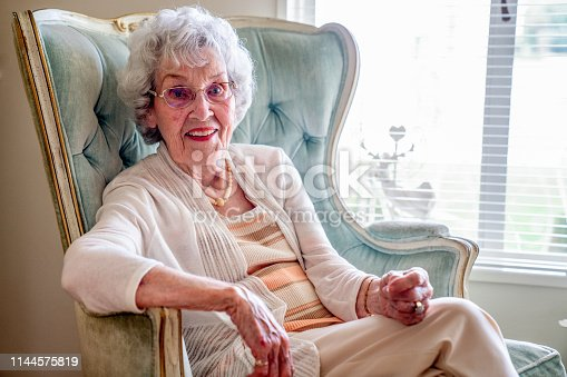 istock 100-Year Old Woman Having a Cheerful Conversation in Her Home 1144575819