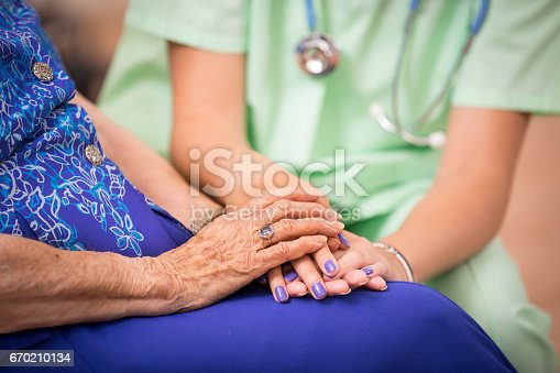 istock 100-Year-Old woman and her home healthcare nurse. 670210134
