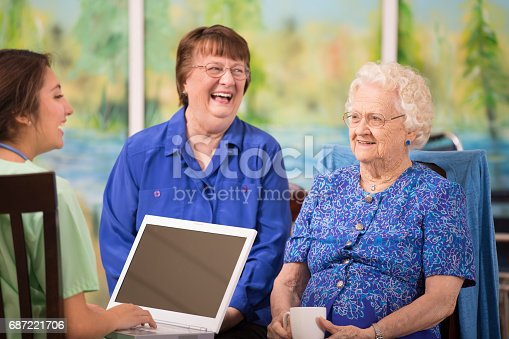 100 year old female patient talks with her Latin descent home healthcare nurse about treatment options in nursing home or home setting.  Her older daughter joins the discussion.  Nurse uses laptop computer.