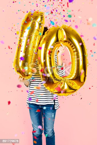 istock 10th anniversary celebration party girl with golden balloons 891729678