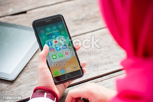 535970955 istock photo BANGKOK, THAILAND- 10th August 2019 : Hands of Islamic woman use Iphone 7 plus with social media application of facebook, youtube, google search, instagram, twitter, linked in, line whatsapp, and pinterest 1169675168
