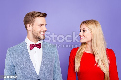 istock 14-february concept. Lovely cheerful stylish attractive romantic couple look to each other make big white beaming smile isolated on shine purple violet background 1053866570