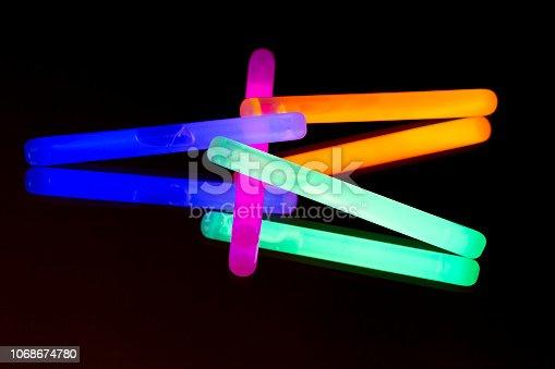 1029436214 istock photo 17/11/2018Colorful fluorescent light neon big glow stick on mirror reflection black background 1068674780
