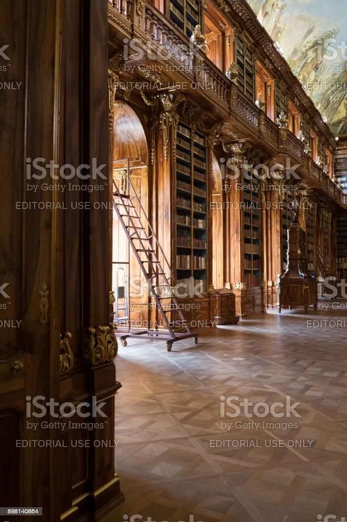 17th century Theological Hall, Library of the Strahov Monastery in Prague. Ladder leaning against the carved wooden bookcases. stock photo