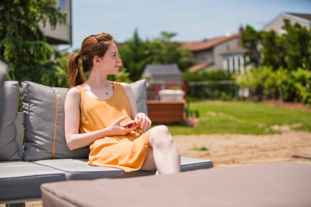 17-years-old beautiful long-haired girl resting on the porch at the backyard - foto stock