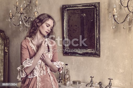 18th centure woman in a castle applying perfume