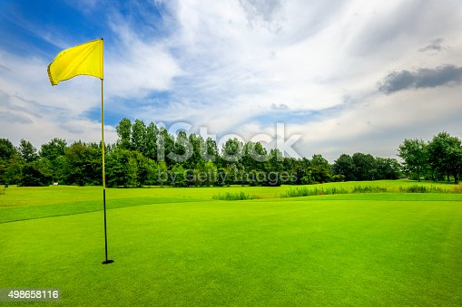 golf course with yellow flag on 18th hole at cloudy sky