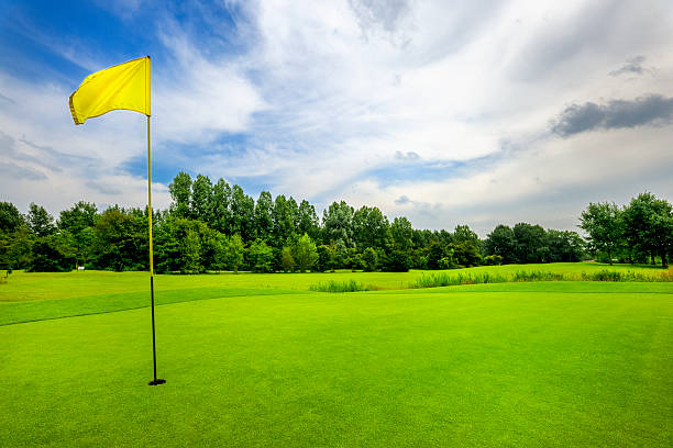 18th hole on golf course golf course with yellow flag on 18th hole at cloudy sky green golf course stock pictures, royalty-free photos & images