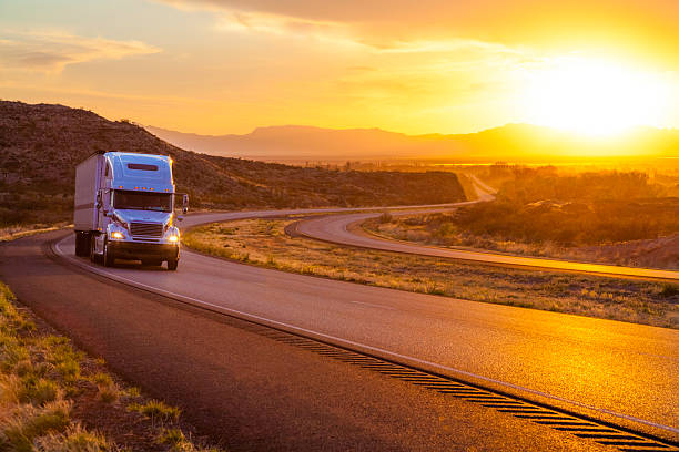 18-wheeler tractor-trailer truck on interstate highway at sunset stock photo