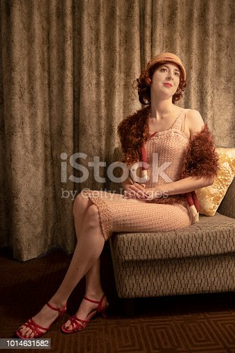 Young woman in 1920s flapper dress with fox fur and cloche sitting in a chair.