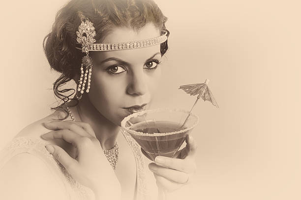 1920s vintage woman in sepia Beautiful young vintage 1920s woman with headband and flapper dress drinking a cocktail diva human role stock pictures, royalty-free photos & images