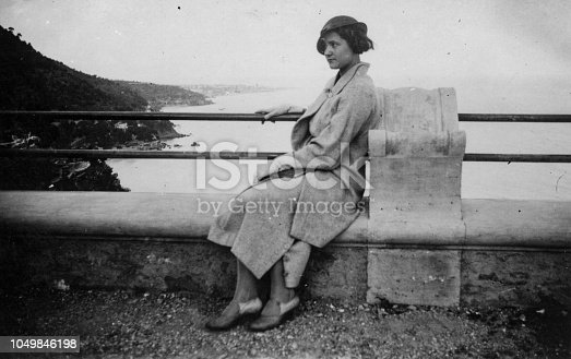 Cute young woman relaxing on the seafront. 1930s black and white film. Alassio, Liguria. Italy