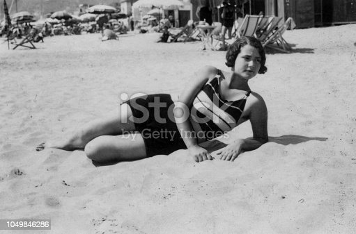 Cute young woman lying on the beach with swimsuit. 1930s black and white film. Alassio, Liguria. Italy