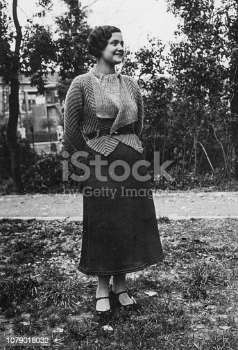 istock 1930s. Florence Tuscany Italy young woman portrait in the home meadow 1079018032