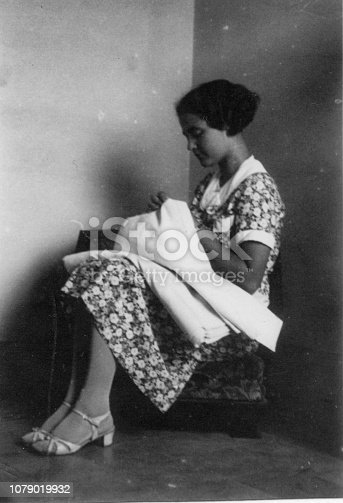 Young woman weaving inside her apartment with elegant italian typical culture dresses. 1930s black and white film. Florence Tuscany. Italy
