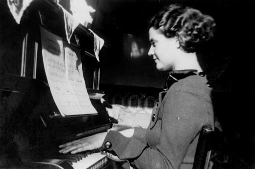 istock 1930s italian woman portrait playing piano 1079018094