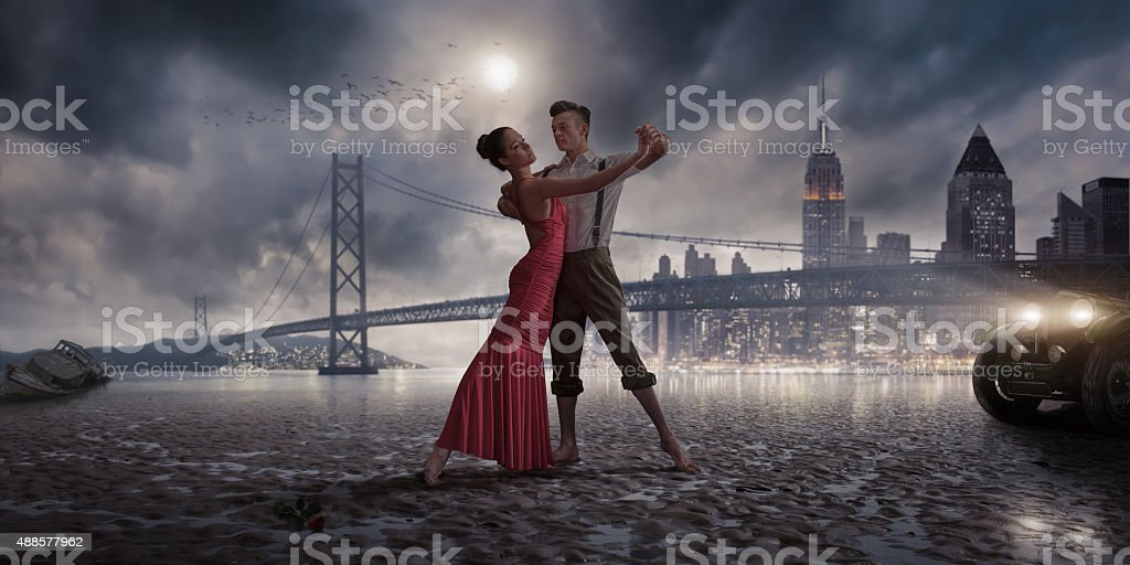 1940s Vintage Dancers on a Moonlit Beach Near City Lights stock photo