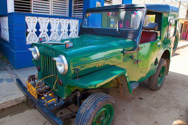 1950s Green Willys Jeep Baracoa, Cuba, March 20, 2013: This 1950s 2-door green Willys Jeep is parked on a quiet street in Baracoa, Cuba, one afternoon in March 2013. willys stock pictures, royalty-free photos & images