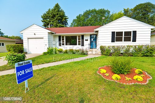A 1950s mid-century modern bungalow style house in the mid-west of United States for sale with sale sign on lawn. The real estate featuring attached garage, picture windows and a well landscaped front yard and driveway.