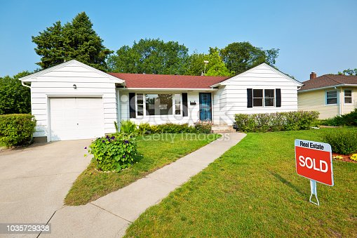 A 1950s mid-century modern bungalow style house in the mid-west of United States for sale with SOLD sale sign on lawn. The real estate featuring attached garage, picture windows and a well landscaped front yard and driveway.