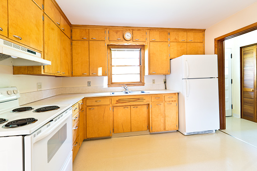 An empty vacant 1950s mid-century modern bungalow style house in the mid-west of United States with old fashion period kitchen.