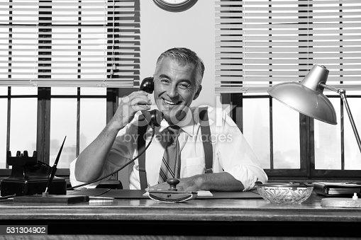Smiling handsome businessman on the phone working at desk, 1950s vintage office.