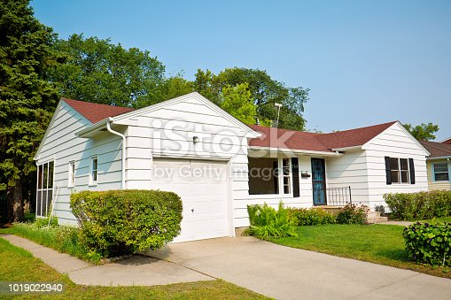A 1950s mid-century modern bungalow style house in the mid-west of United States. The real estate featuring attached garage, picture windows and a well landscaped front yard and driveway.
