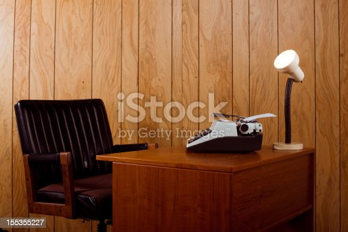 Horizontal image showing a retro 1970s office. Complete with a leather chair, typewriter and desk lamp.