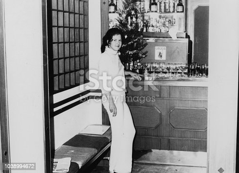 1970s Outdoor portrait of a young woman posing inside a typical bar. Black and white taken with 35mm film